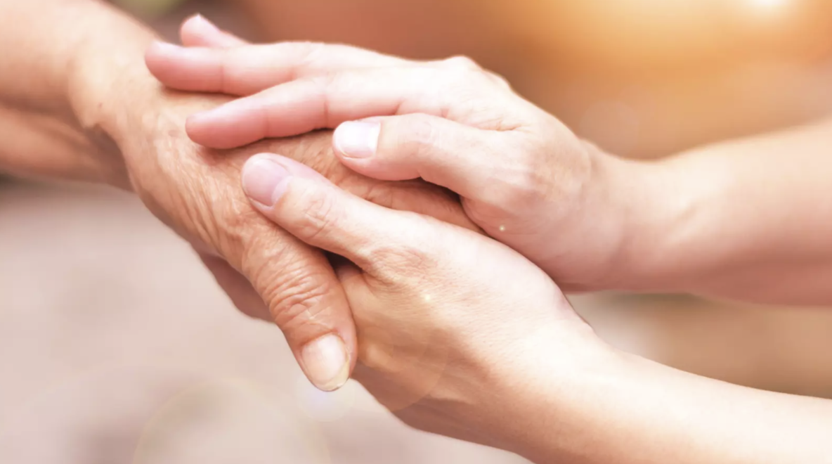 Two younger hands holding an older hand