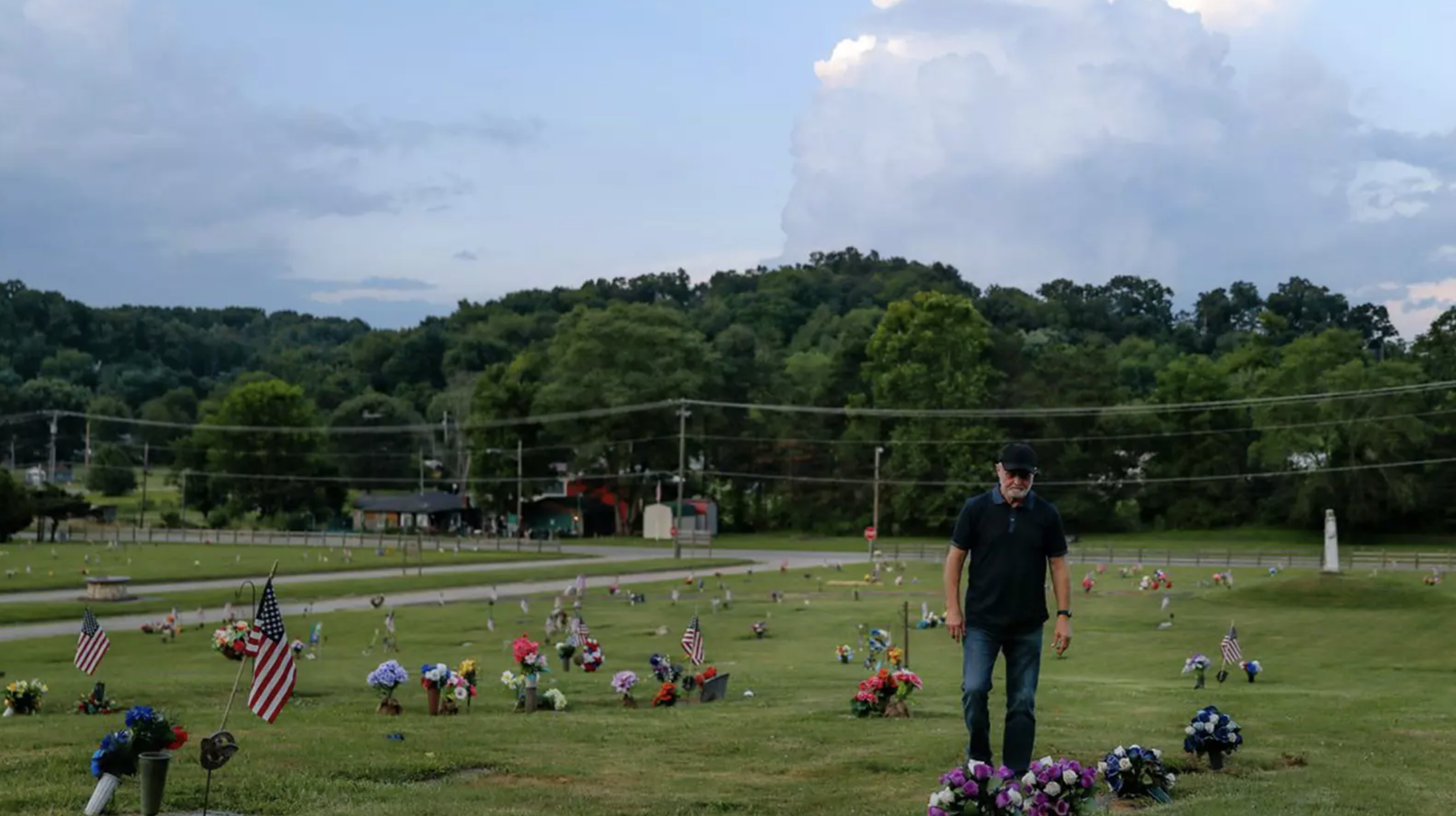 Man stands in cemetery with flowers