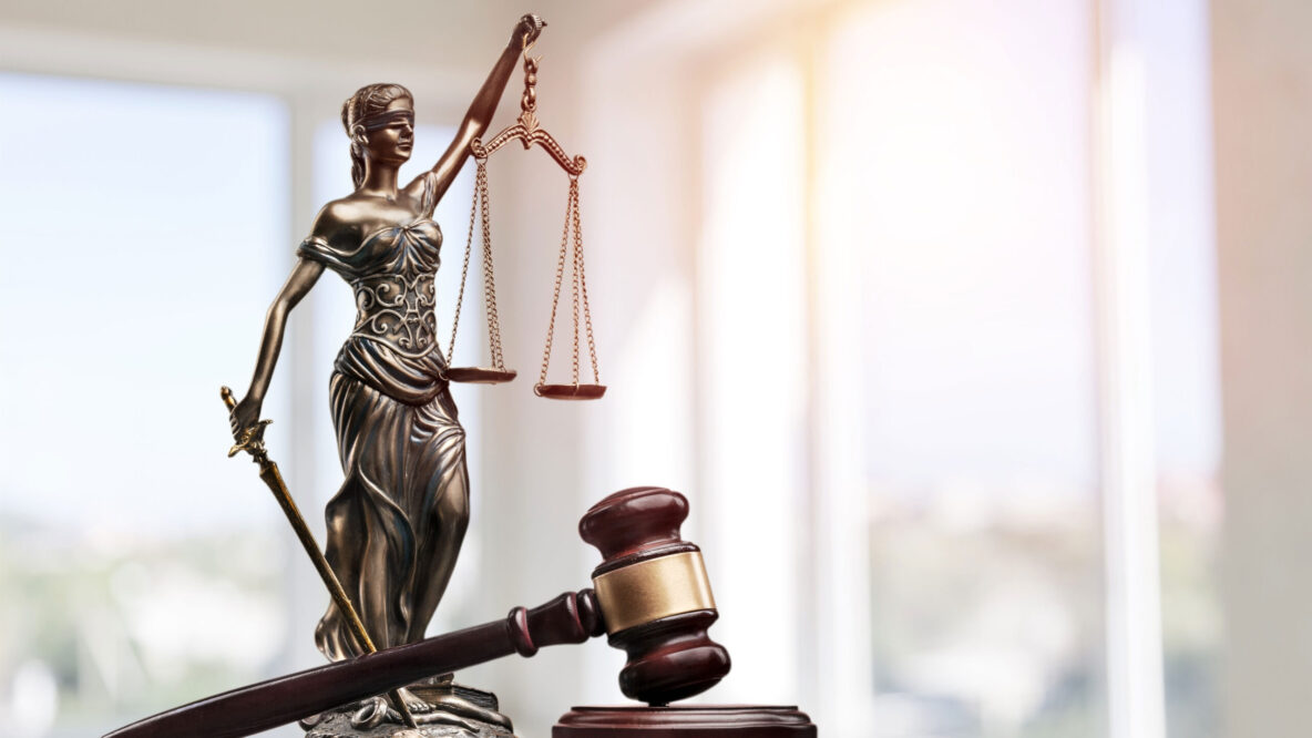 Gavel in front of a statue of blind Justice