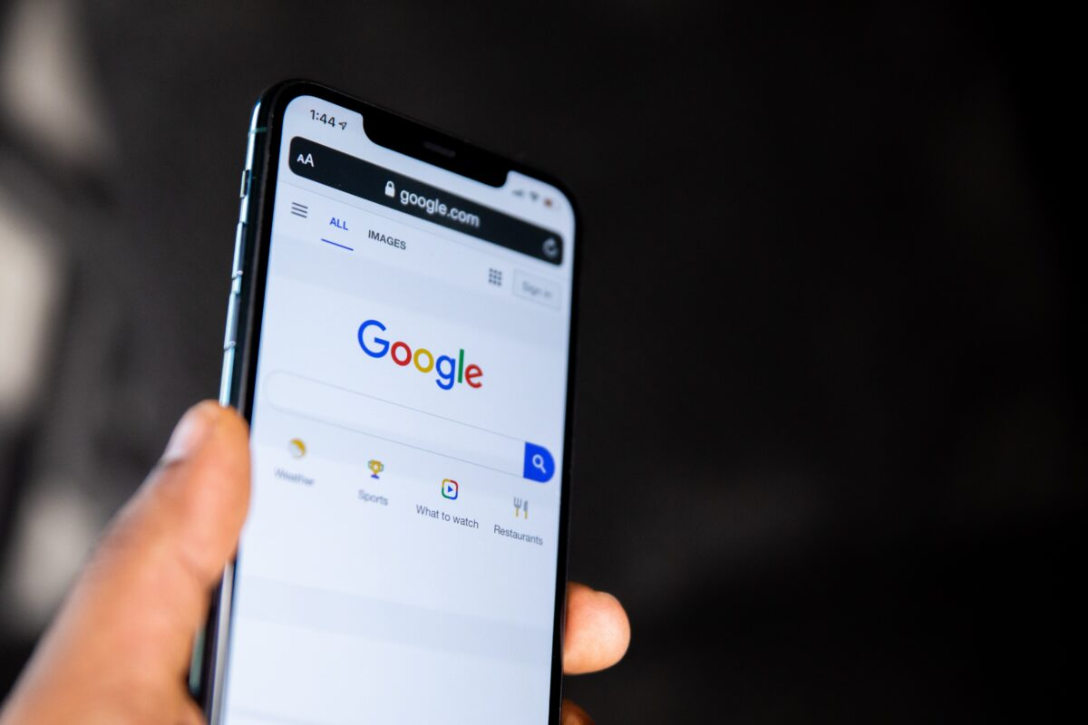 Hand holding a phone displaying Google